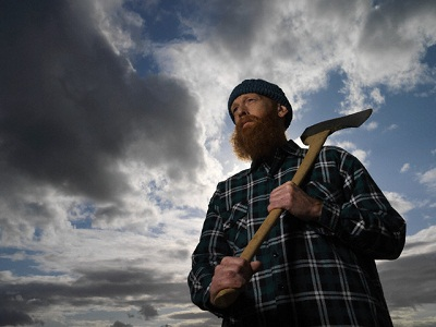 Man Carrying Axe --- Image by © Bob Thomas/Corbis